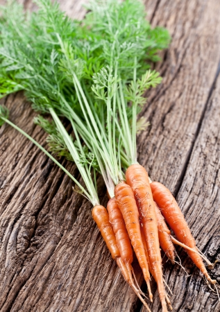 Carrots with leaves on a old wooden table Stock Photo - 18398839