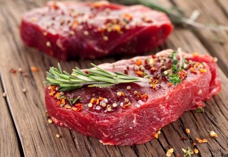 어두운 나무 테이블에 원시 쇠고기 스테이크
