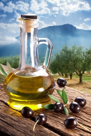 oil bottle: Black olives with bottle of oil on a wooden table on a background of olive garden