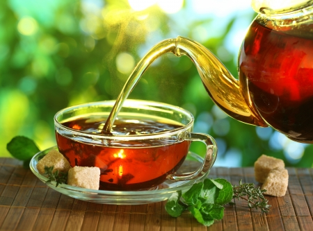 cup: Pouring tea from a teapot into a cup on a blurred background of nature.
