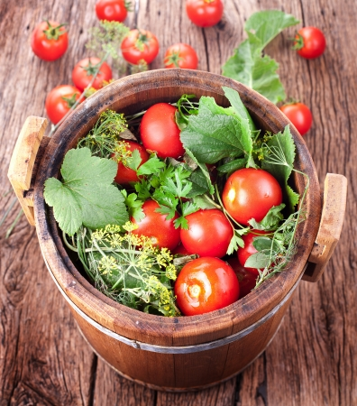 Barrel of pickled tomatoes on an old wooden table. Stock Photo - 18398837