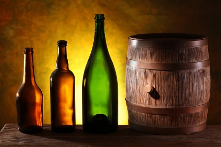 distillery: Wooden barrel with colors bottles on a dark yellow background.