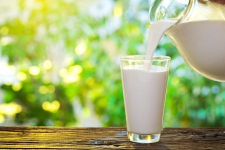 vaso de leche: Verter la leche en el vaso sobre el fondo de la naturaleza Foto de archivo