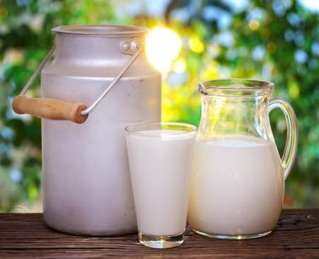 melk glas: Melk in verschillende gerechten op de oude houten tafel in een buitenomgeving