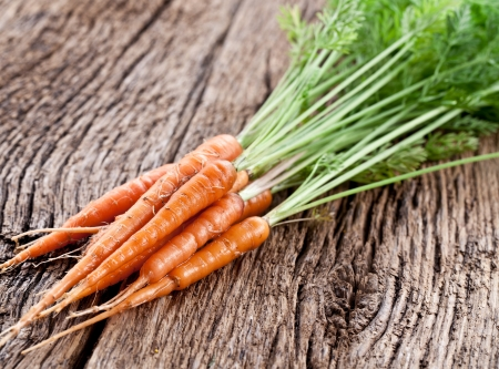 Carrots with leaves on a old wooden table. Stock Photo - 19005299