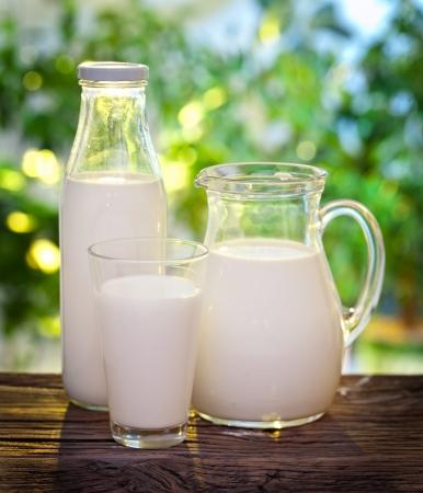 leche y derivados: Leche en varios platos en la mesa de madera vieja en un entorno al aire libre. Foto de archivo
