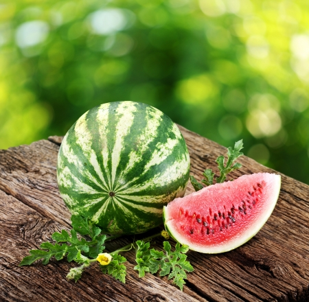 Watermelon with a slice and leaves on a wooden table  Background - blur of nature   photo
