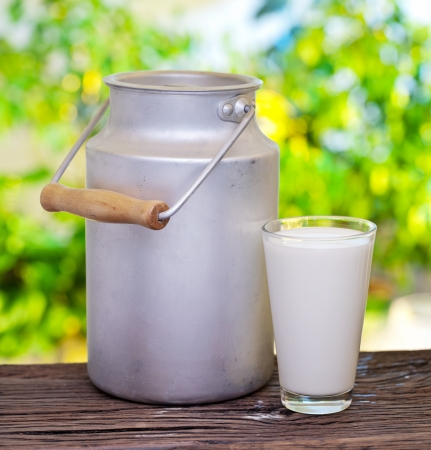 lait: Lait en aluminium peut et verre sur la vieille table en bois sur la configuration ext�rieure.