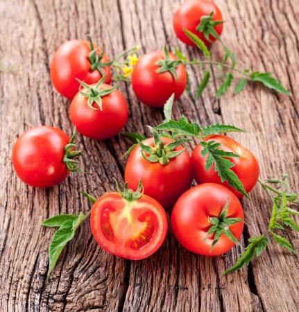 pomidory: Pomidory, gotowane z ziół do zachowania na starym drewnianym stole. Zdjęcie Seryjne