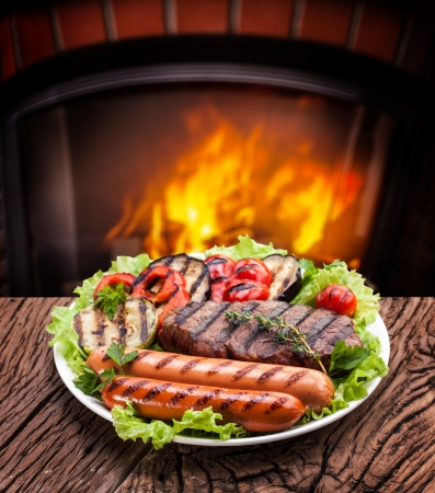 sizzling: Products grill: steak, sausage and vegetable on a plate.