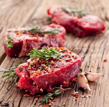 Rohes Rindfleisch Steak auf einem dunklen Holztisch.