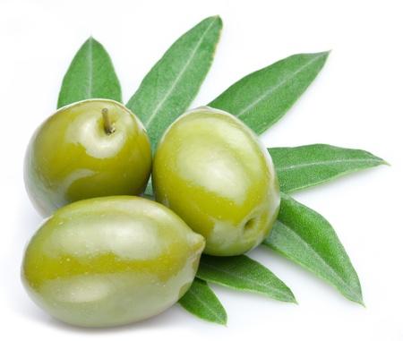 Grüne Oliven mit Blättern auf einem weißen Hintergrund. Standard-Bild