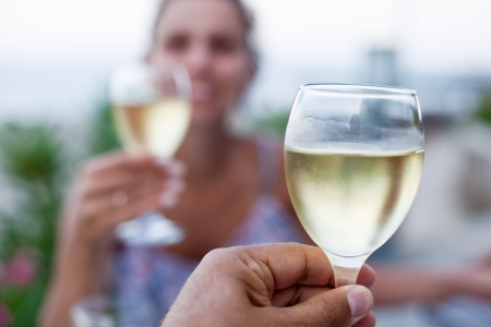 woman drinking wine: Toast for two to the sea during dinner.