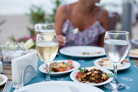 catering service: Romantic dinner with white wine. In the background a girl is out of focus.