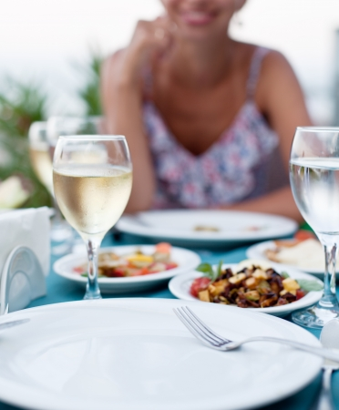 Romantic dinner with white wine. In the background a girl is out of focus. photo