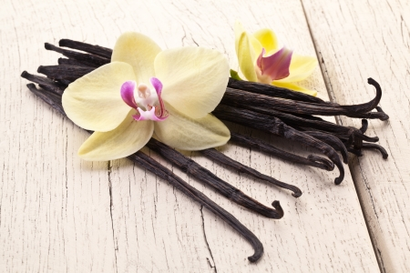 vanilla bean: Vanilla sticks with a flower on a white wooden table.