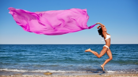 Sexy athletic brunette jumping on the beach with a large pink cloth. Фото со стока