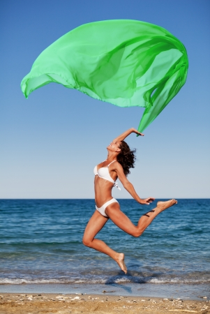 Sexy athletic brunette jumping on the beach with a large green cloth.