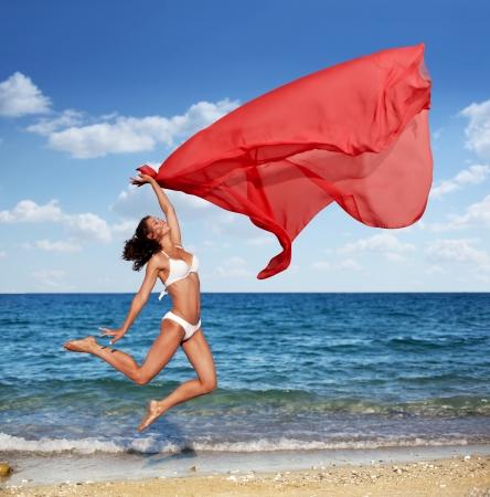 tela seda: Sexy atlético salto morena en la playa con un paño rojo grande. Foto de archivo