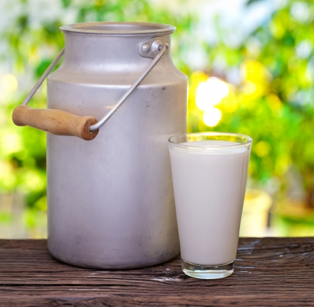 Milk in aluminum can and glass on the old wooden table on outdoor setting. photo