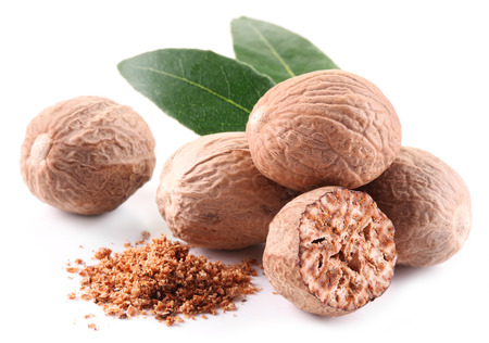 ground nuts: Nutmeg with leaves on a white background.