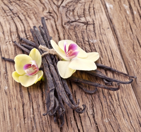 indian bean: Vanilla sticks with a flower on a wooden table. Stock Photo