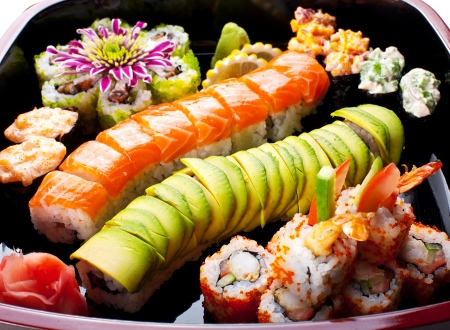 avacado: Different sushi rolls on a black plate.