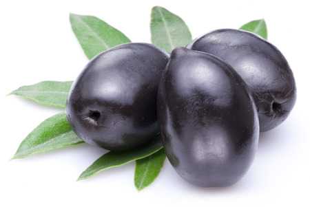 Three large ripe black olives with leaves isolated on a white. Standard-Bild