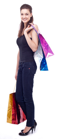Happy young girl keeping shopping bags in her hands. Isolated on a white background. photo