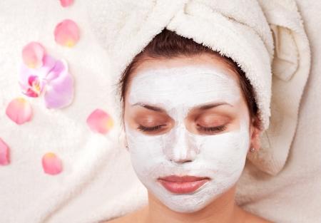 Junge Frau mit Ton-Gesichtsmaske im Beauty-Salon. Standard-Bild