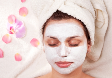 beauty mask: Young woman with clay facial mask in beauty salon. Stock Photo