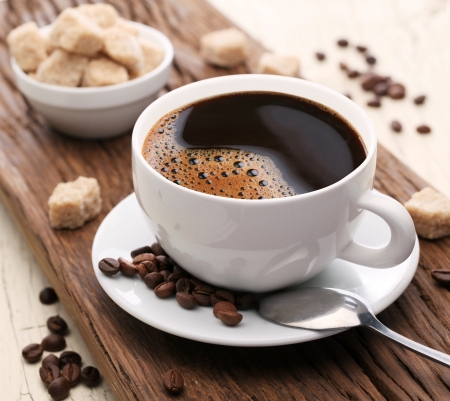 Cup of coffee with brown sugar on a wooden table. photo