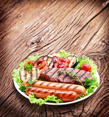 chorizos asados: Filete a la plancha, salchichas y verduras sobre hojas de lechuga sobre una mesa de madera.