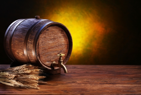 beer barrel: Old oak barrel on a wooden table. Behind blurred dark background.
