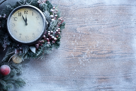 Christmas clock over snow wooden background. Five to twelve. photo