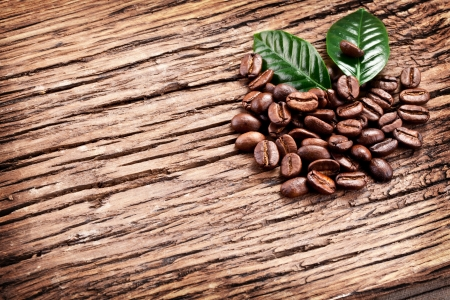 Roasted coffee beans and leaves isolated on a wooden background. Stock Photo - 23321307