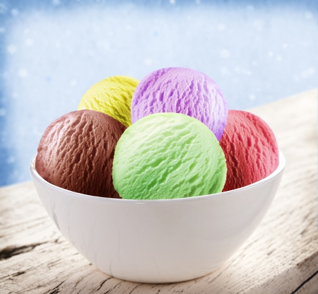 Colorful ice-cream scoops in white cones over snow background. photo