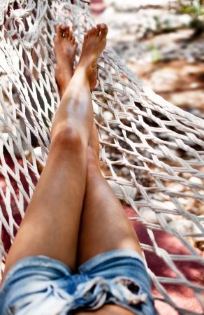 Young woman in hammock. Closeup shot of legs.