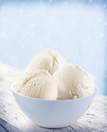 Vanilla ice-cream scoops in white cup over snow background. photo