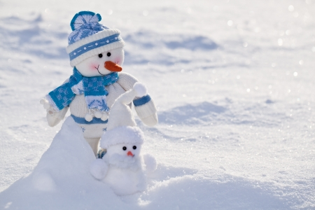 snowbank: Two little snowmen with carrot nose in the snow. Stock Photo