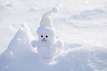 snowbank: Little funny snowman near bank of snow. Stock Photo