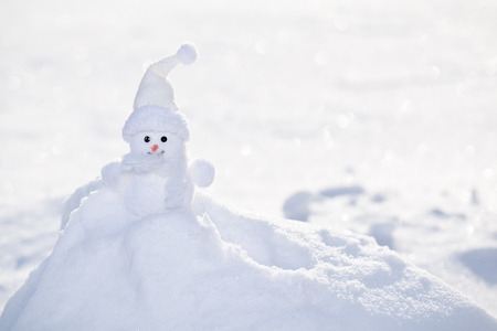 snowbank: Little white snowman near snowbank. Stock Photo