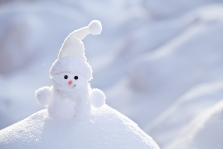 snowbank: Little funny white snowman in the snowbank.
