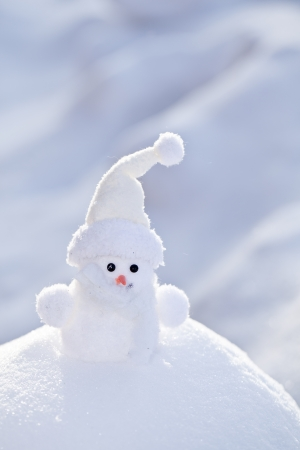 snowbank: Little white snowman on the snowbank. Stock Photo