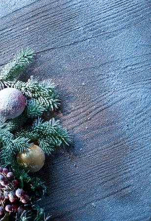Christmas decoration with fir and baubles over wooden background. photo