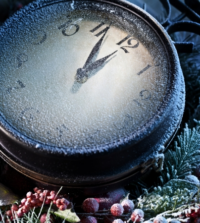 New Year clock powdered with snow. Five to twelve. photo