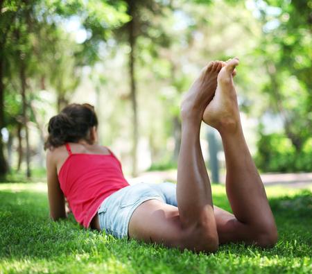 piernas mujer: mujer joven en la hierba. La cara en desenfoque. Foto de archivo