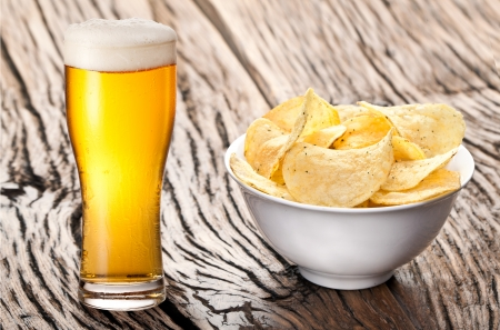 Potato chips  and glass of beer on a wooden table. photo