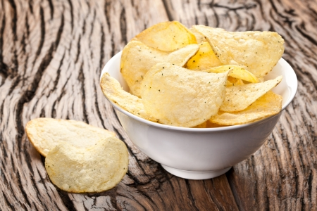 Potato chips in a bowl on a wooden table. photo