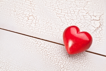 craquelure: D�a de San Valent�n. Coraz�n rojo en una mesa de madera craquelado blanco.